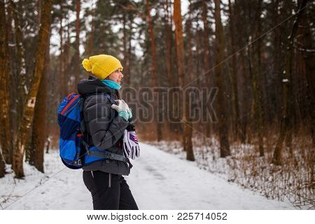 Side View Of Girl With Backpack In Winter Forest In Afternoon
