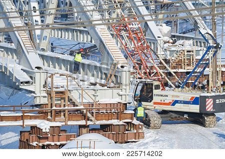 Moscow, Feb. 01, 2018: View On Workers With Caterpillar Crane Building A Metal Bridge Across Rail Wa