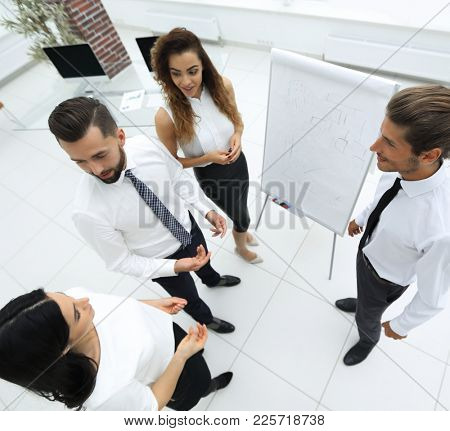 business team standing in front of a flipchart.