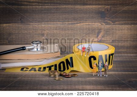 Health Care And Medical Background. Yellow Caution Tape On A Wood.