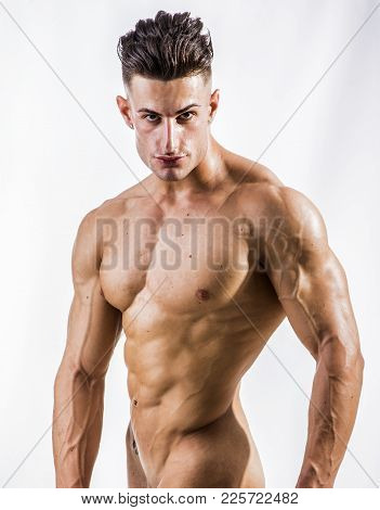 Good Looking Young Gym Fit Man Showing His Sexy Six Pack Abs While Looking Up, Isolated On White Bac