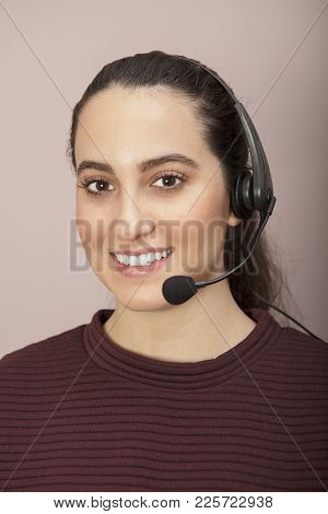 Attractive Friendly Young Woman Wearing A Headset And Smiling At The Camera In A Concept Of Customer