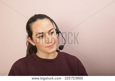 Dark-haired Woman Sitting With Headset In Call Center In A Concept Of Customer Services, Call Center