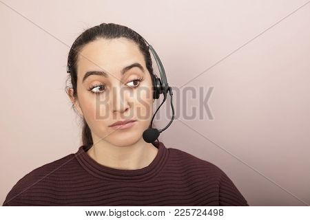 Sceptical Help Desk Or Call Center Operator Listening To A Call Looking To The Side With Raised Eyeb
