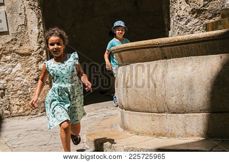 Saint-paul-de-vence, France - July 13, 2016. Alley With Stone Arches, Children And Fountain In Saint