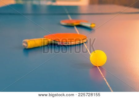 Sports Competitions In Table Tennis. Two Old Orange Tennis Rackets And A Yellow Ball Lying On A Blue