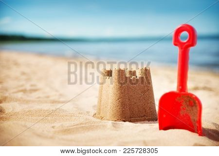 Sandcastle With A Shovel On The Sea In Summertime. Seashore On Beautiful Day. Sand On The Beach And