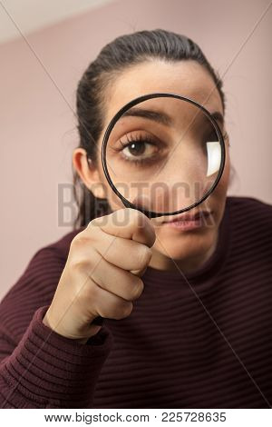 Woman Searching For Clues Or Conducting An Investigation Or Search Peering Through A Handheld Magnif
