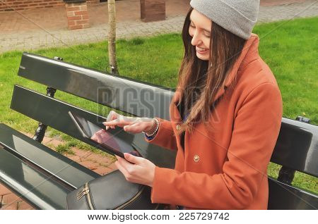 Beautiful European Woman Sitting On The Bench Outside And Using A Black Tablet. Autumn. Dressed In A
