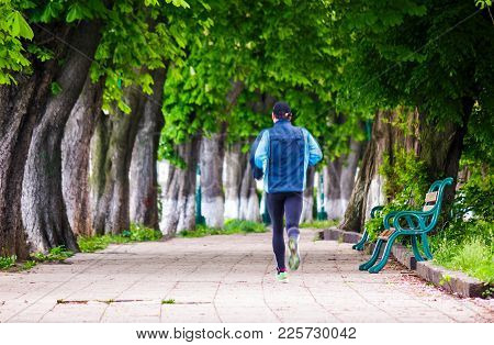 Man Having A Morning Run On Alley Of Kiev Embankment In Uzhgorod. Lovely Chestnut Alley In Summertim