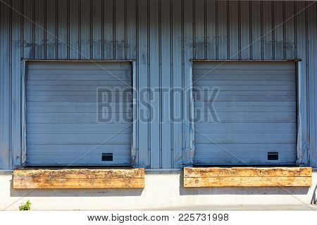 Closeup Of Two Closed Shutter On A Loading Dock Under Sunny Day