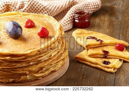 A Pile Of Thin Hot Pancakes With Fruits Of Strawberries And Plums, A Few Pancakes With Jar Of Jam On