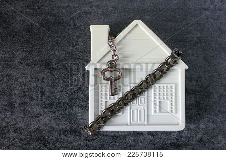 Small White House, Chain And A Decorative Key On A Dark Background. Concept  -  Risks, Lose Property