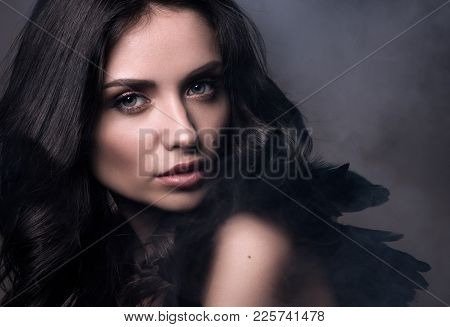 Black Angel In A Cloud Of Smoke. Beauty Closeup Portrait In Dark Tones. Sexy Young Woman In Black Wi