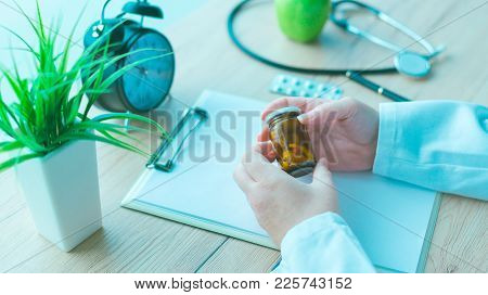 General Practitioner Holding Unlabeled Bottle Of Various Pills And Medication, Generic Drugs Concept