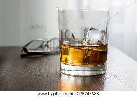 Glass Of Whiskey, Brandy, Cognac With Ice Cubes On Wooden Table Desk With Glassess. Mockup Of Produc
