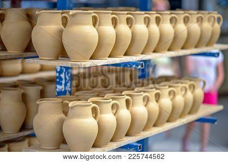 Ceramic Dishware Arranged On Shelf In Pottery Workshop