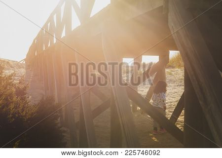 Little Girl Playing Between The Wooden Pillars Of A Catwalk That Leads To The Beach With The Sunset