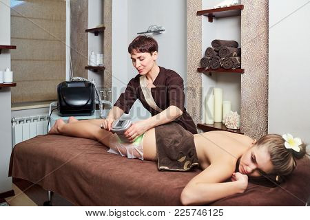 A Woman Lying Down Doing Cryolipolysis Treatment In A Spa Center.