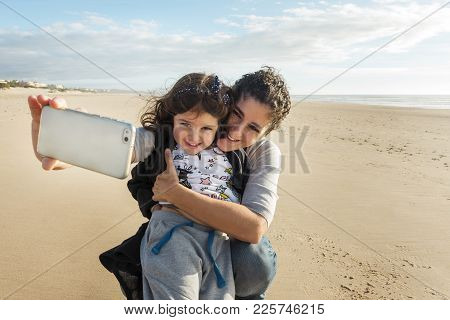 Happy Mother Taking A Selfie With Her Smiling Daughter On The Beach With Her White Smart Phone In Th