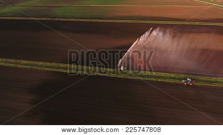 Irrigation Equipment Watering Freshly Seeded Field.irrigation At Sunset.irrigation Of Farmland To En