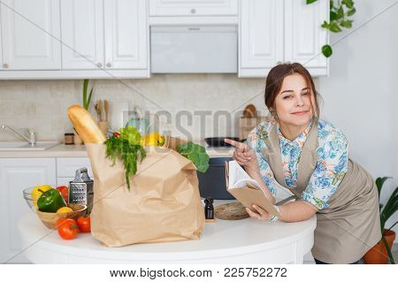 Young Housewife Reading A Book Of Vegetarian Recipes.