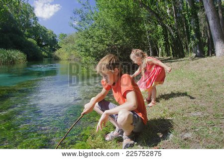 Siblings Summer Recreation Activity Outdoor Game On Italian Tirino River Bank In Sunny Day