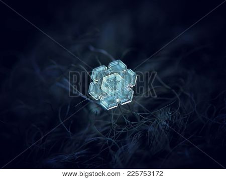 Real Snowflake Glowing On Dark Textured Background. Macro Photo Of Real Snow Crystal: Small Star Pla