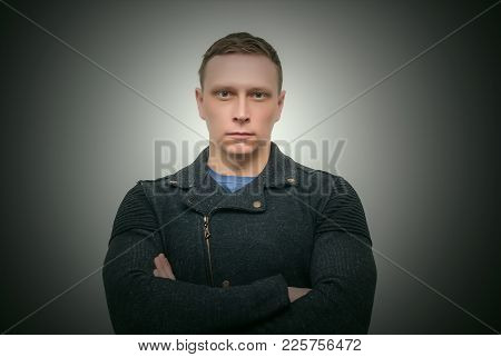 Serious Confident Man Is Standing With Crossed Arms Isolated On Dark Background.