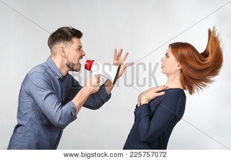 Angry man with megaphone scolding his wife on light background