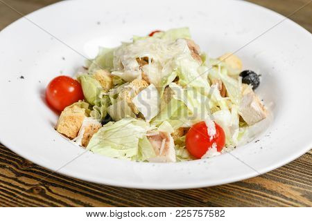 Chicken Caesar Salad With Lettuce Leaves In White Bowl On Wooden Table.