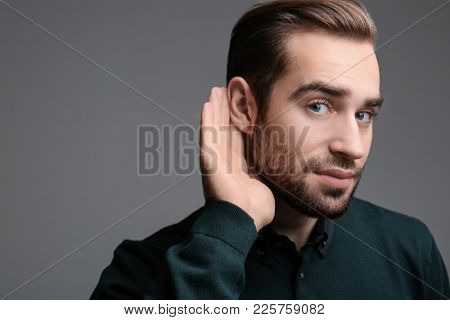Young man with hearing problem on grey background
