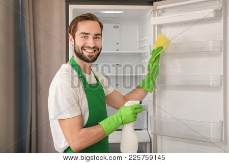 Man cleaning empty refrigerator in kitchen