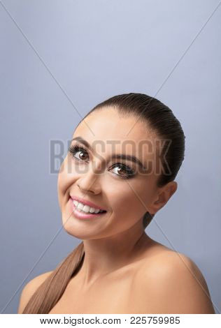 Beautiful young woman with eyelash extensions on color background