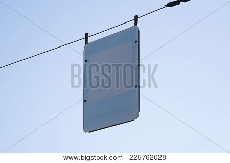 Blank Road Sign Over Blue Sky Background. Empty Street Sign Template Hanging On Wires.