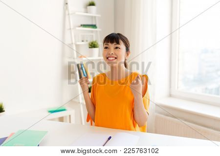 education, success, learning and people concept - happy smiling asian student girl with notebooks making fist pump gesture at home