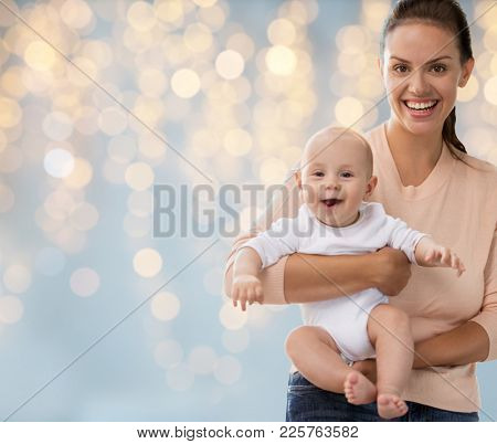 family, motherhood and people concept - happy mother with little baby boy over holidays lights background