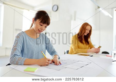 architecture, business and people concept - female architect with blueprint working at office