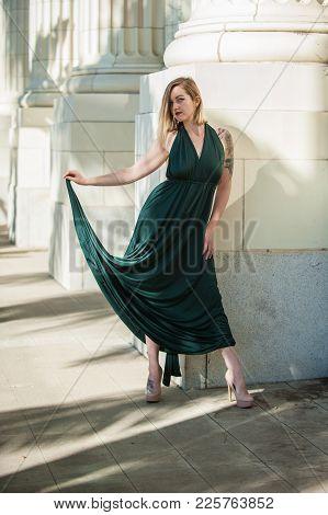 Blond Alternative Model Holding A Delicate Curve Of Emerald Green Halter Top Dress.  Shot At Ventura