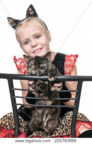 Girl In A Cat Costume Sits On A Chair And Holds A Live Cat, Isolated On A White Background