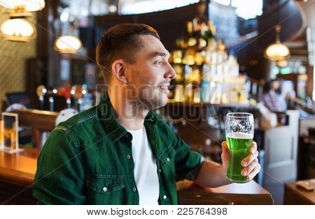people, leisure and st patricks day concept - happy young man drinking green beer at bar or pub