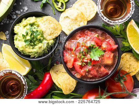 Latinamerican Mexican Food Party Sauce Guacamole, Salsa, Chips And Tequila On Black Table. Top View.