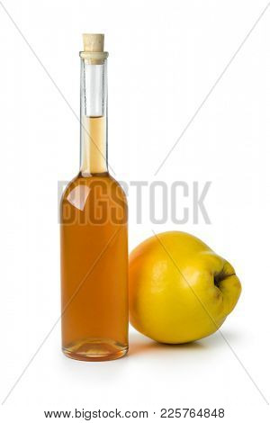 Glass bottle of homemade quince liqueur isolated on white background