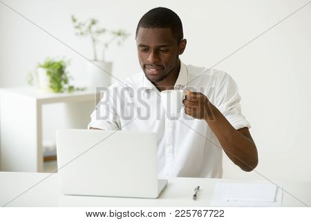 Smiling Attractive African American Man Enjoying Coffee While Using Laptop Sitting At Home Office De