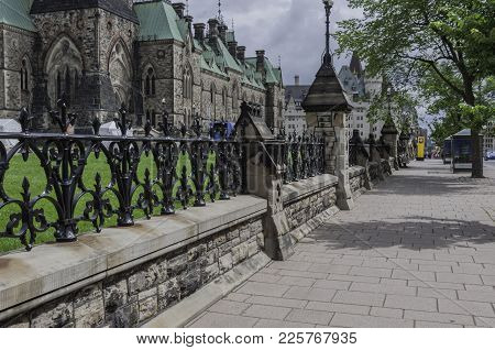 Sidewalk In Ottawa, Ontario Canada With Black Wrought Iron Fence Above A Stone Wall Barrier On The S