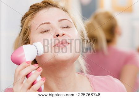 Deep Cleaning Face Tools Concept. Happy Woman Using Facial Cleansing Brush Machine Feeling Relaxed