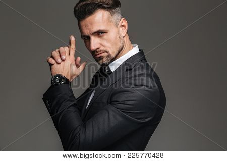 Photo in profile of elegant adult man 30s in black suit looking on camera with tricky sight and holding hands like gun isolated over dark gray background