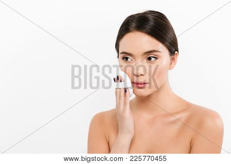 Image of cute woman with clean healthy skin applying concealer or powder on face with cosmetic sponge isolated over white background