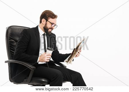 Portrait of mature male employer in suit and eyeglasses holding takeaway coffee and reading newspaper while sitting on chair isolated over white wall
