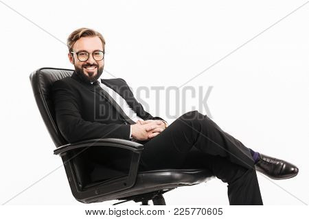 Portrait of cheerful male employer in suit and eyeglasses smiling while sitting on black armchair in office isolated over white wall